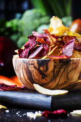Vegan snacks, multicolored vegetable chips in wooden bowl, background from set of fresh farmer vegetables, still life, selective focus
