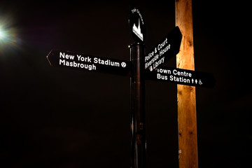 Signpost to Rotherham Town Centre, Bus Station, Library, Police Station, Court, Riverside House & Rotherham United Stadium (New York) - at night, with a street light background