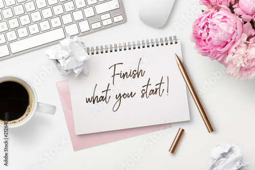 finish what you start - business concept. Notepad / ring binder, crumpled paper balls, mug with coffee and office supplies on a white feminine styled desktop, top view - 212645425