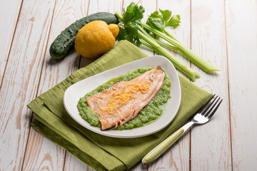 trout over cucumber cream decorated with lemon peel