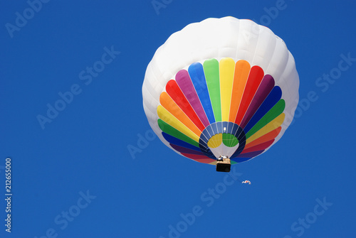 White and colorful hot air balloon. Background blue sky