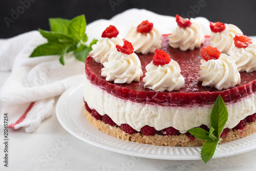 Foto Murales Raspberry cheesecake with whipped cream and fresh raspberries on a white plate.Copy space.