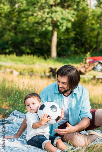 happy father and toddler son playing with football ball at picnic