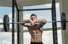 """Постер, картина, фотообои """"Sportsman, athlete with muscles looks attractive. Sport and gym concept. Man with torso, muscular macho lean on barbell, window on background. Man with nude torso in gym enjoy his sporty lifestyle"""""""