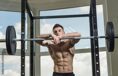 Sportsman, athlete with muscles looks attractive. Sport and gym concept. Man with torso, muscular macho lean on barbell, window on background. Man with nude torso in gym enjoy his sporty lifestyle - 212661051