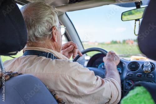 an elderly man is driving a car