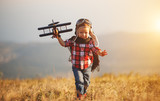 Child pilot aviator with airplane dreams of traveling in summer  at sunset - 212674044