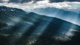 Beautiful nature landscape of mountains with snow and green forest. Sunbeams, rays through clouds