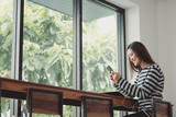 Happy Asia woman using mobile listening music near window at cafe restaurant,Digital age casual lifestyle,life outside home concept.