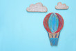 cardboard Hot air balloon cut from paper and painted over wooden blue background.