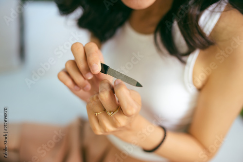 Aluminium Manicure Portrait of a smiling pretty young woman painting friend's nails over white background