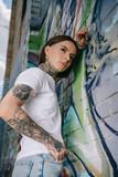 low angle view of stylish tattooed girl posing near wall with colorful graffiti