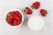 Ripe strawberries in bowl, cup of milk and three strawberries