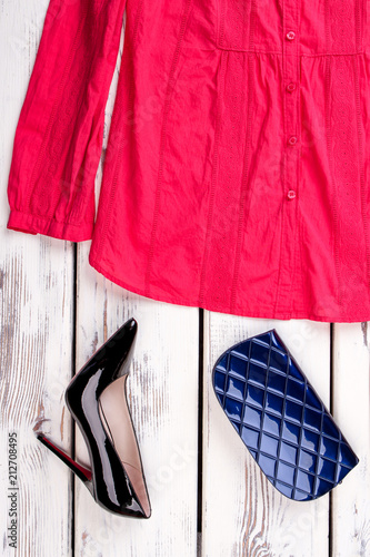 Horizontal cropped view pink shirt on white wooden background. Blue women's wallet and black shoe with heel. - 212708495