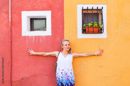 Fototapeta Happy young woman in white dress with blue flowers, posing near red and orange house in Burano Island.