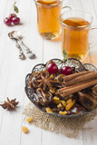 Oriental sweets, dried fruit dates and raisins, cinnamon and star anise in a plate. Turkish tea in glasses on a wooden background.
