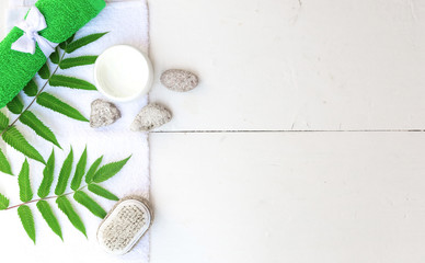 Spa beauty cosmetics on white marble table from above . Copy space. Flatlay. a jar of cream, leaves, flowers and a towel on a wooden background © zatevakhin