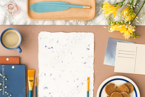 Top view on desk with yellow flowers, painting brush on paper and cup of coffee. Real photo - 212719878