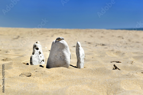 white pebbles crashed in the sand of the beach under blue sky - 212721015
