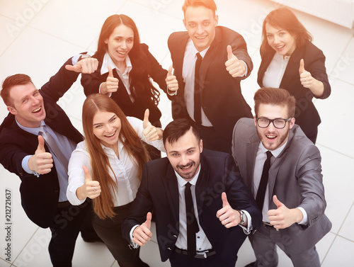 Leinwanddruck Bild successful business team holding up a thumbs up