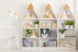 Lamps above white chair next to shelves with wooden triangles and plants in bright interior. Real photo