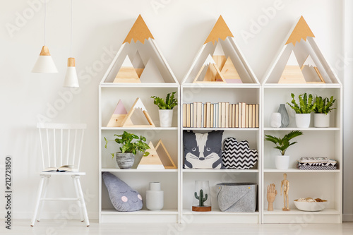 Fototapeta Lamps above white chair next to shelves with wooden triangles and plants in bright interior. Real photo