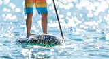 Detail of young man standing on paddleboard. - 212722010