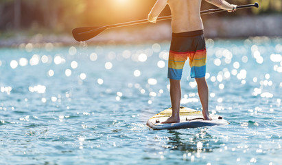 Detail of young man standing on paddleboard.