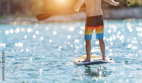 Foto Murales Detail of young man standing on paddleboard.