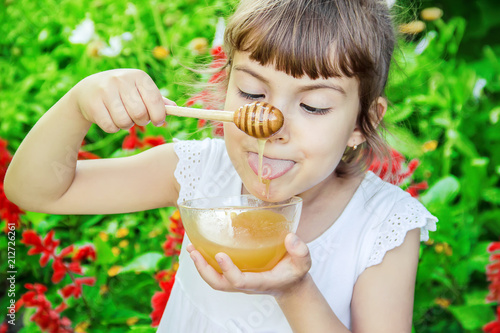 Leinwanddruck Bild The child eats honey. Selective focus.