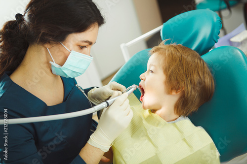 Dentist preparing drill tooth to child, little patient obediently opened his mouth, sitting on chair. - 212728004