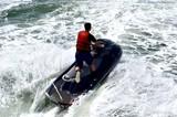 Jet skier running waves on a black jet ski on the Florida Intra-coastal Waterway.