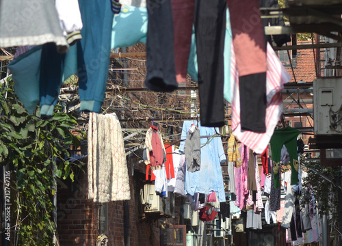 Fotobehang Shanghai Clothes have been hung to dry between the buildings of a back street in Shanghai. Air conditioning units can also be seen.