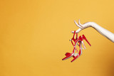 Fototapety Hand with high hell shoes in studio on yellow background