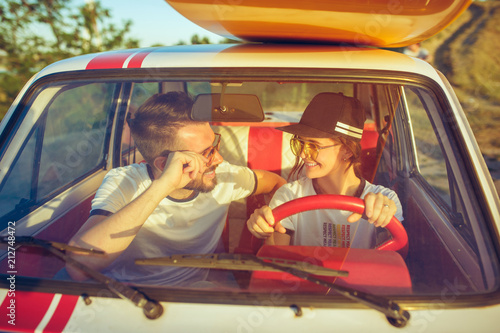 Laughing romantic couple sitting in car while out on a road trip at summer day - 212748472