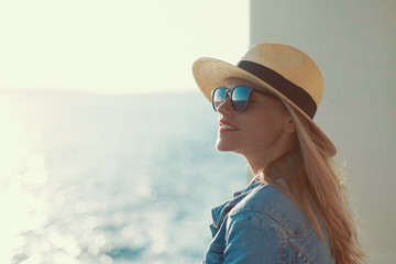 Blonde traveler woman portrait in hat on cruise ship, looking away