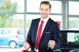 Seller or car salesman in car dealership with key presenting his new and used cars in the showroom - 212757892