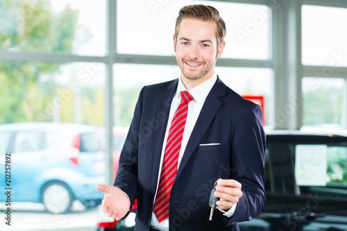 Sprzedawca lub sprzedawca samochodów w salonie samochodowym z kluczem przedstawiający swoje nowe i używane samochody w salonie