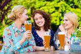 Happy friends toasting with beer in garden pub - 212763804