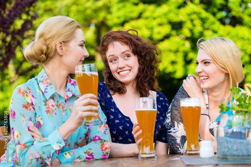 Fototapeta Happy friends toasting with beer in garden pub