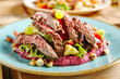 Salad with Grilled Prime Beef or Thick Slices of Marbling Steak on Blue Plate - 212766261