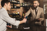 Bartender accepting credit card at bar counter - 212767444