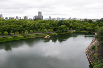 Aerial view of moat around castle park, Osaka business district and spectacular mountains surrounding the city from Osaka Castle. © Kenishirotie