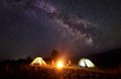 Leinwanddruck Bild - Night camping in mountains. Bright campfire burning between two backpackers, man and woman sitting opposite each other in front of illuminated tents under amazing dark blue starry sky and Milky way