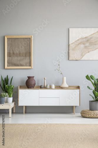 Biała szafka między roślinami w szarym wnętrzu salonu z plakatami i brązowym dywanem. Prawdziwe zdjęcie