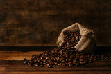 Fototapety bunch of fresh roasted coffee beans with burlap sack on a wooden table. agriculture and drink concept