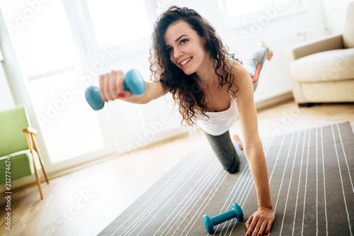 Fotobehang Fitness Young attractive sportswoman doing exercises at home