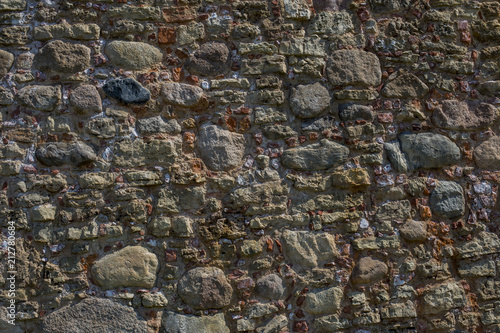 Fototapeta the wall of an old building lined with stones