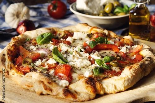 Herzhafte hausgemachte Pizza mit Feta Käse, Tomaten, Oliven und Basilikum - 212787237
