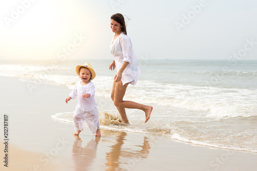 Foto Murales Young beautiful girl in white shirt with little boy in white clothes running on sea water and smiling cheerfully